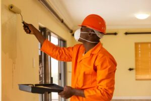african construction worker painting the wall